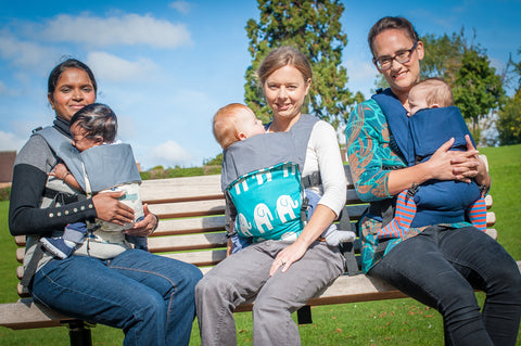 Model Mums and Babies on the park bench. Action Baby Carrier