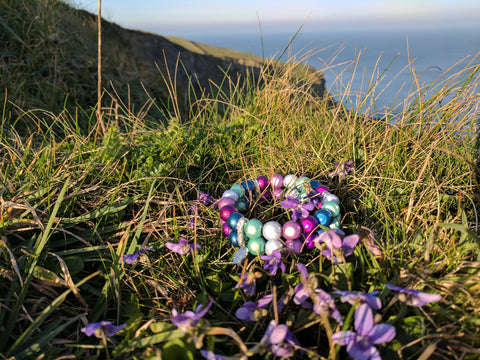 posy spectrum disco bead bracelets on a bed of purple violets