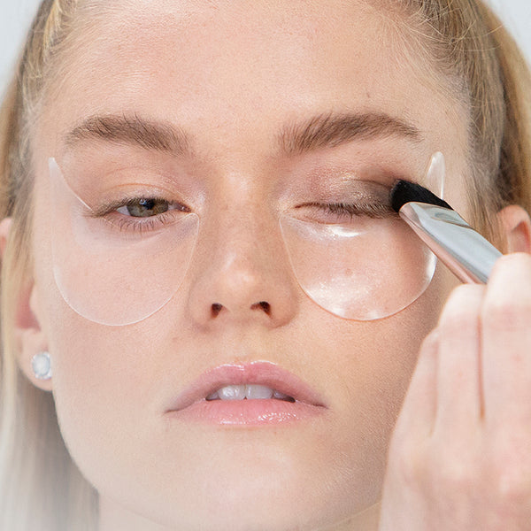 even eye stencils under eyes on model as she puts on her eyeshadow