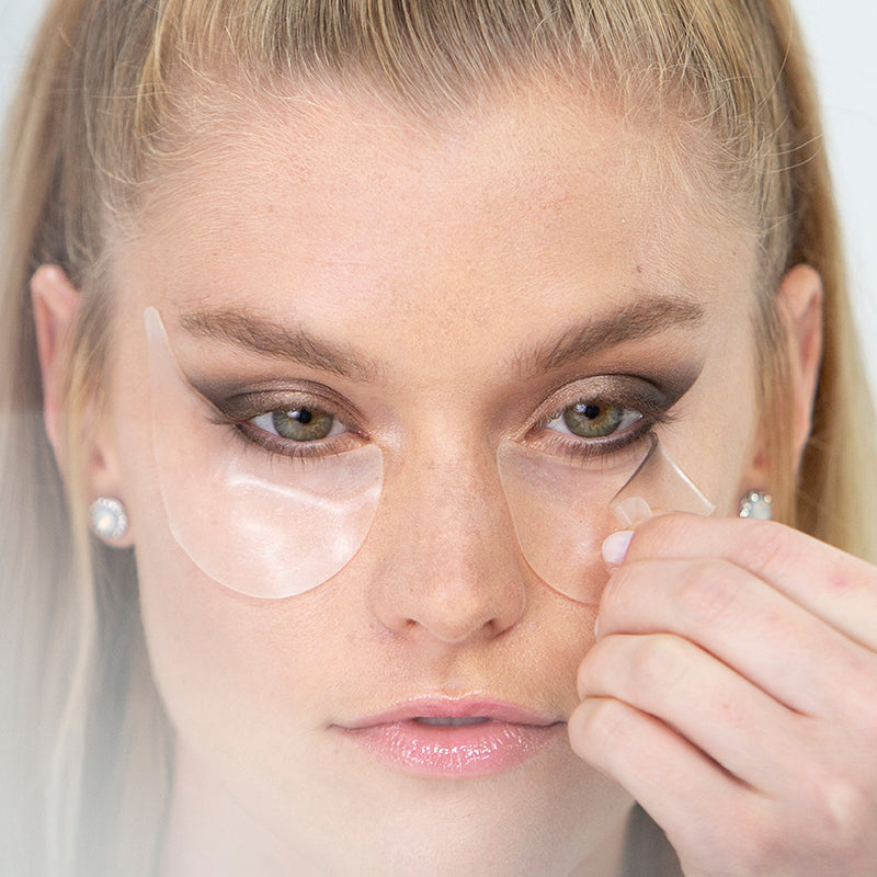 model peeling gently off her under eye to show perfect eyeshadow look