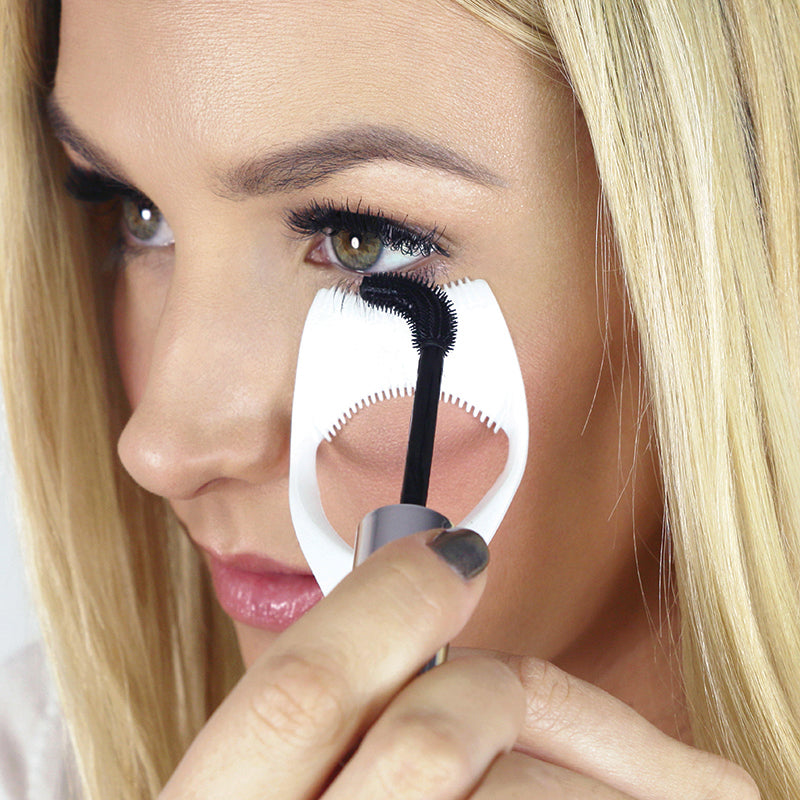 mascara shield in use on lower lashes with mascara wand bent protecting under eye on model