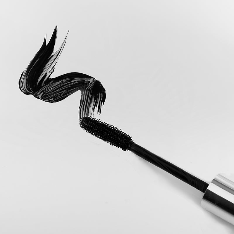 flex and curl mascara wand showing black formula on flat surface