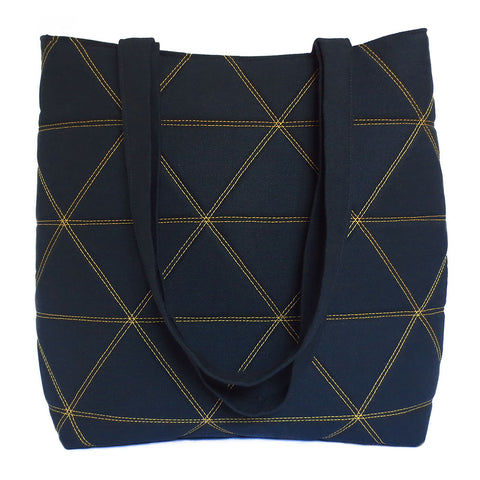 "black denim and vinyl vegan tote bag, sized for everyday use. Gold stitching in bold triangle motif on black denim. Two large pockets, double strap with 12"" drop."