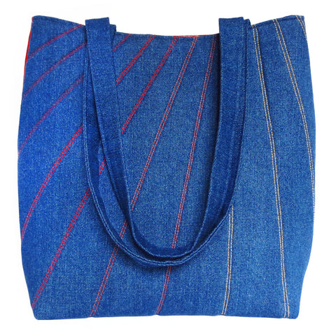 dark blue denim tote stitched with lines in shades of red, orange, and gold. back is red vinyl.