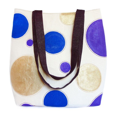 Tote bag featuring natural canvas hand painted with giant polka dots in gold, purple, and blue, paired with dark blue denim flecked with gold thread.