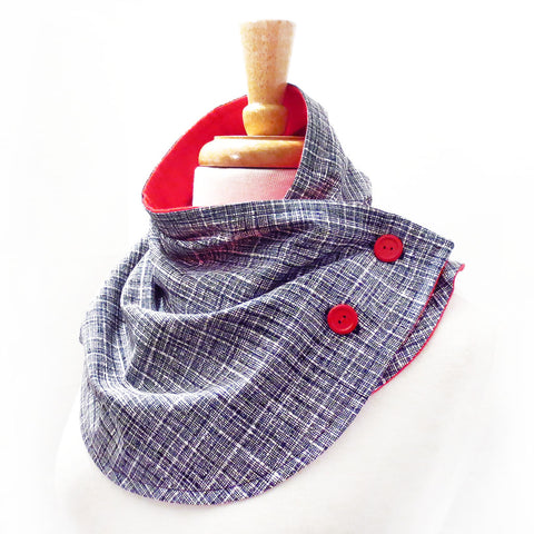 button scarf in black and white crosshatch print, lined in bright red flannel with two red buttons