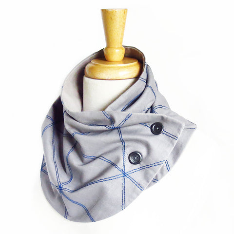 Fabric button scarf with triangle motif stitched in purple thread on light gray cotton. Lined in light gray flannel with two hand painted buttons.