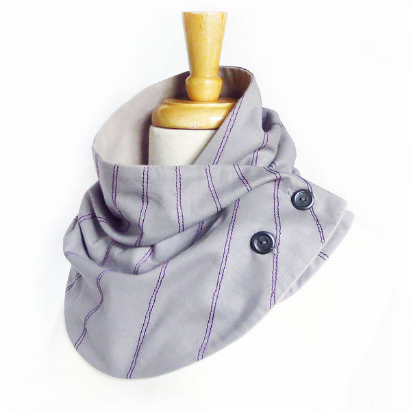 Fabric button scarf with purple stitching on light gray, lined in light gray flannel with two hand painted buttons.