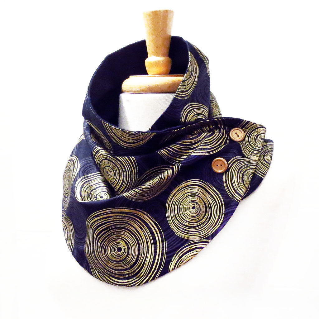 button scarf in a very bold circular geometric print in black, gray, and metallic gold. Buttoned closed with two gold hand painted buttons.