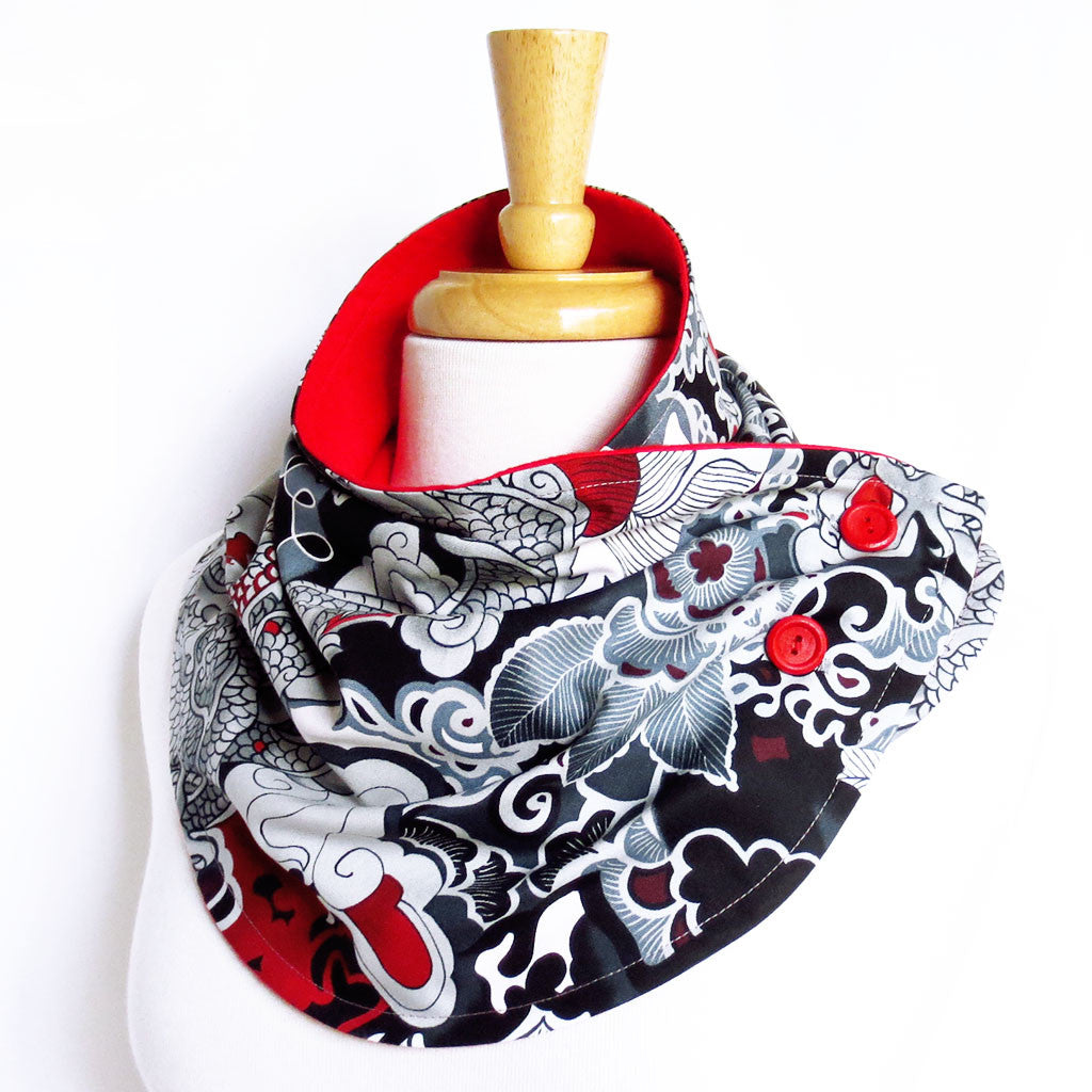 the lucille button scarf is in a bold, Chinese-style dragon print in black, gray, and red, with red hand painted buttons, and red flannel lining