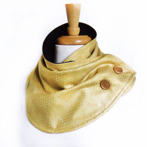 the maya button scarf is in tonal gold print in tiny stars with subtle metallic shine, with gold hand painted buttons, and black flannel lining