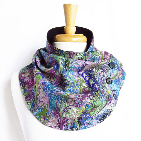 the natalie button scarf is in a classic book marble print in shades of purple, blue, and blue-green, with black hand painted buttons and black flannel lining