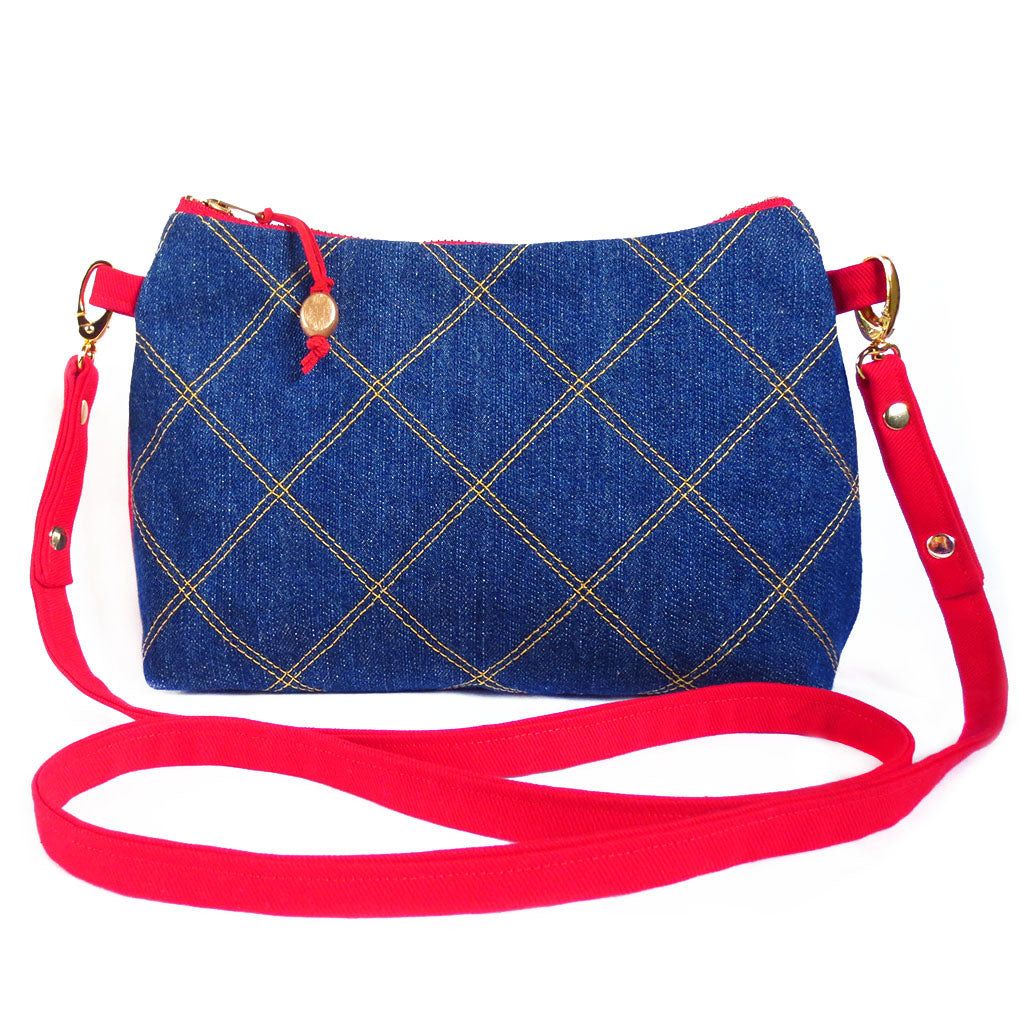 crossbody in dark blue denim quilted with gold thread, with red denim strap and back.