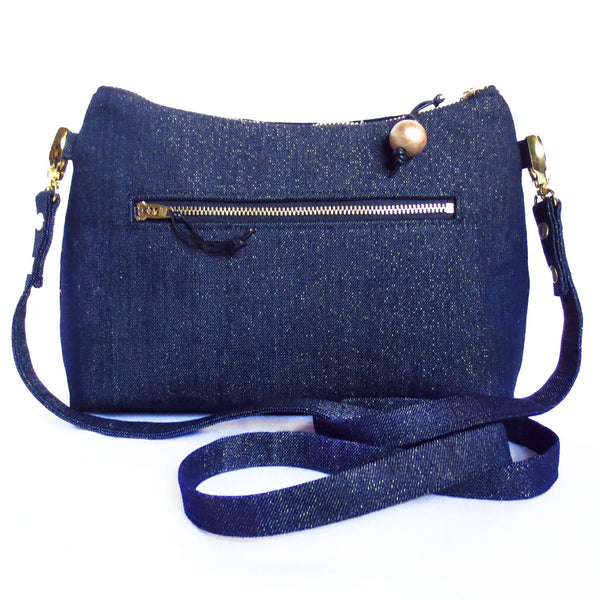 "the back of the calliope crossbody bag is dark denim accented with gold metallic threads, and features a 7"" zippered pocket"