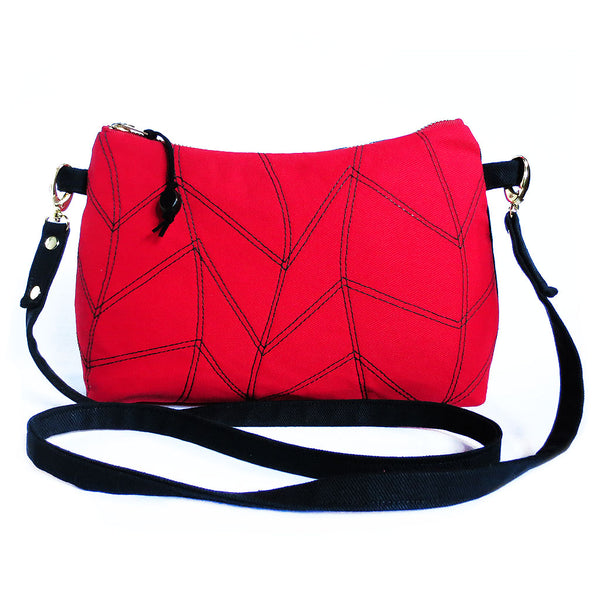 red and black denim crossbody bag with chevron wave motif stitched on front.