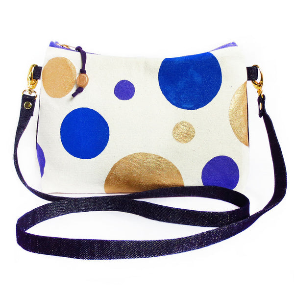 crossbody bag with hand painted polka dots in blue, purple and gold on natural canvas, with dark denim with gold metallic threads