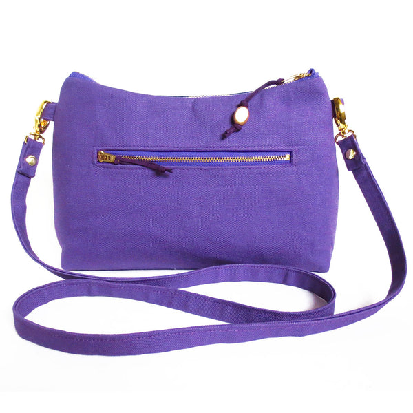 "back view of the lola crossbody bag in bright purple canvas, with a 7"" zipper pocket"