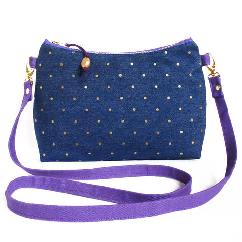 the lola crossbody bag is polka dotted denim and purple canvas