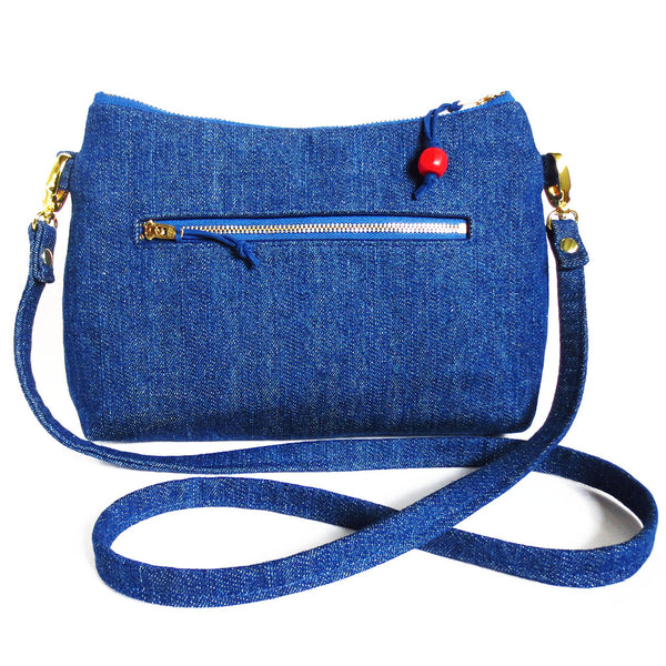 "the back of the persephone crossbody bag is dark blue denim with a 7"" zipper pocket"