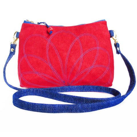 crossbody bag in red ultrasuede and dark blue denim, with a stitched floral motif on the front