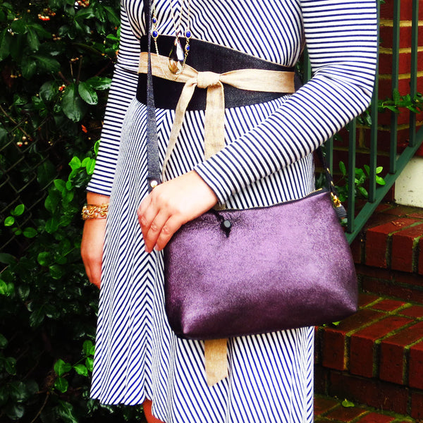 Emily is wearing the raina crossbody bag in purple leather, and the selina wrap belt in denim and gold essex linen.