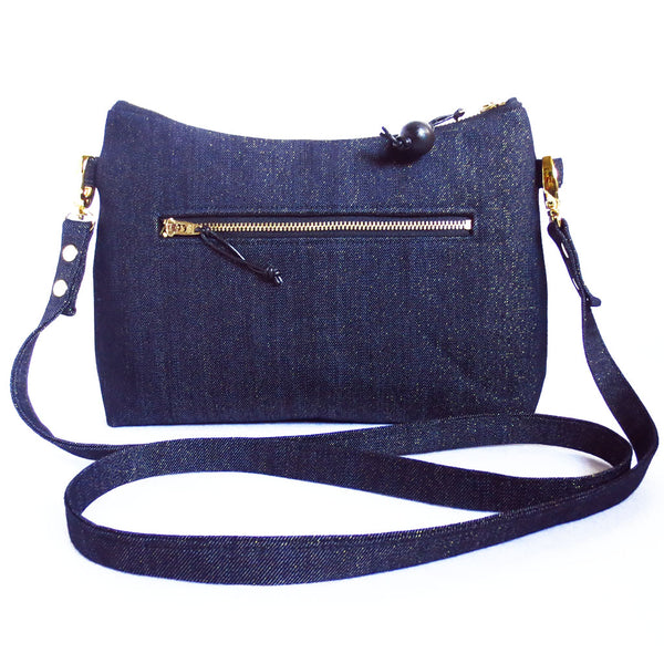"the back of the raina crossbody bag is dark blue metallic denim with a 7"" zipper pocket"