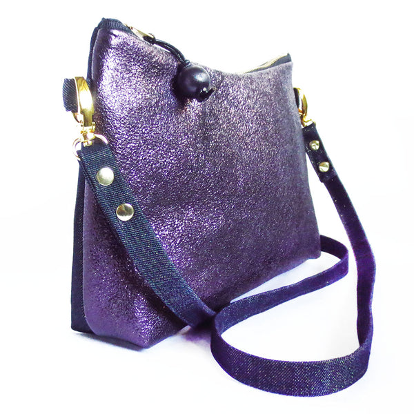 side view of the raina crossbody bag, in purple metallic leather and metallic denim with gold hardware