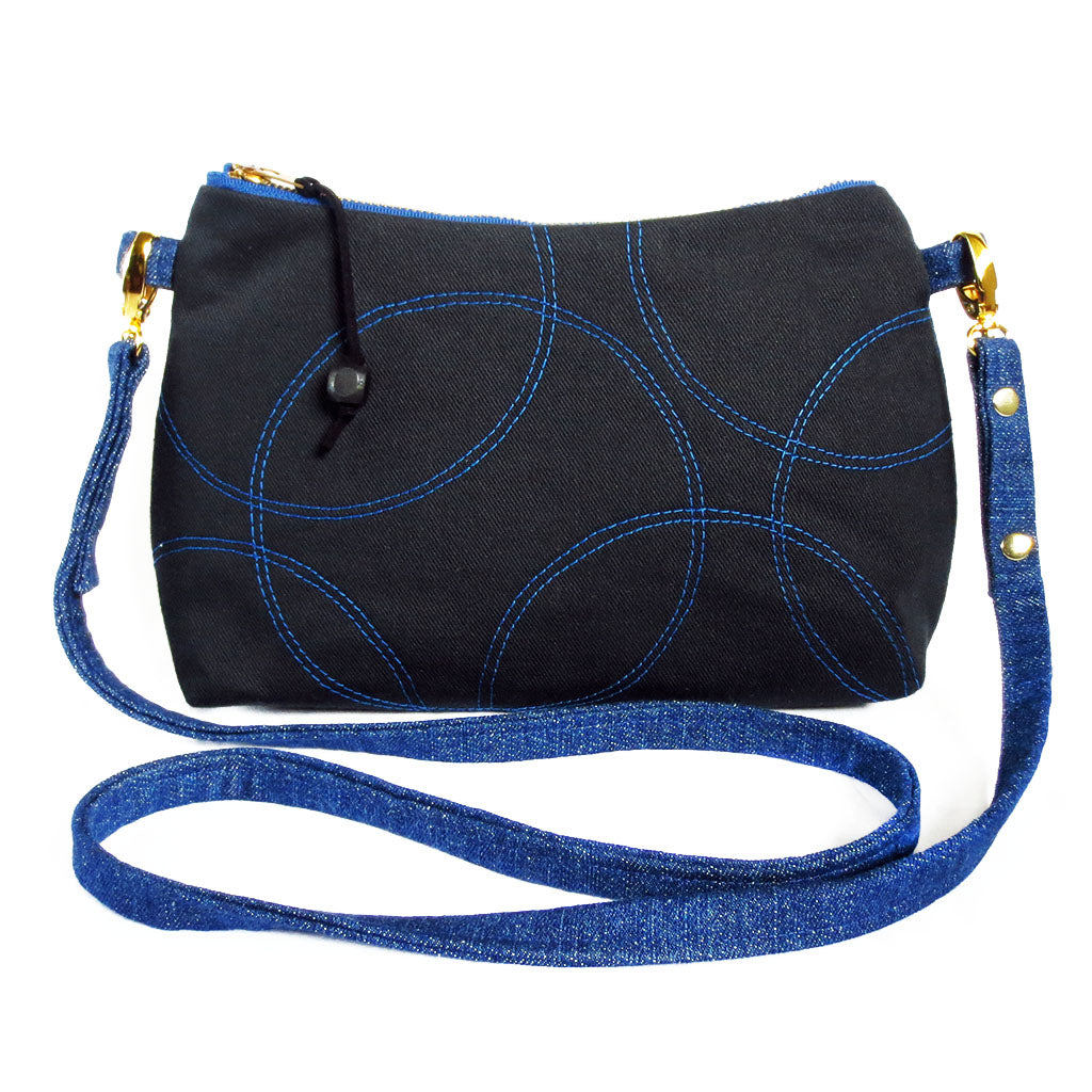 Crossbody bag in black and blue denim. Front is stitched in overlapping circles motif in blue thread on black.