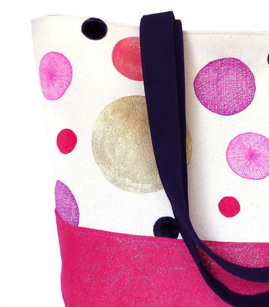 close up of hand painted polka dots on canvas, with black denim and hot pink metallic leather
