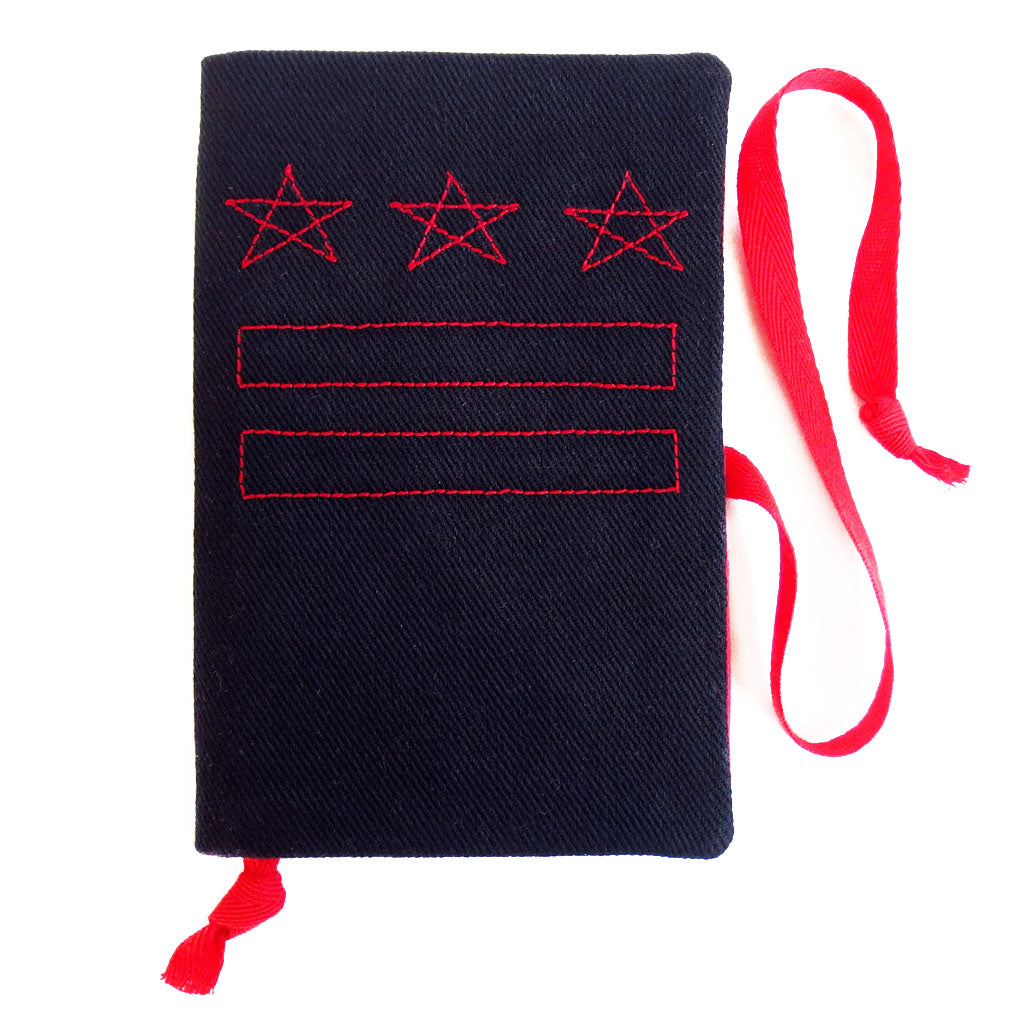 black canvas field notes cover, stitched with the DC flag in red thread, with red fabric book mark and wrap tie