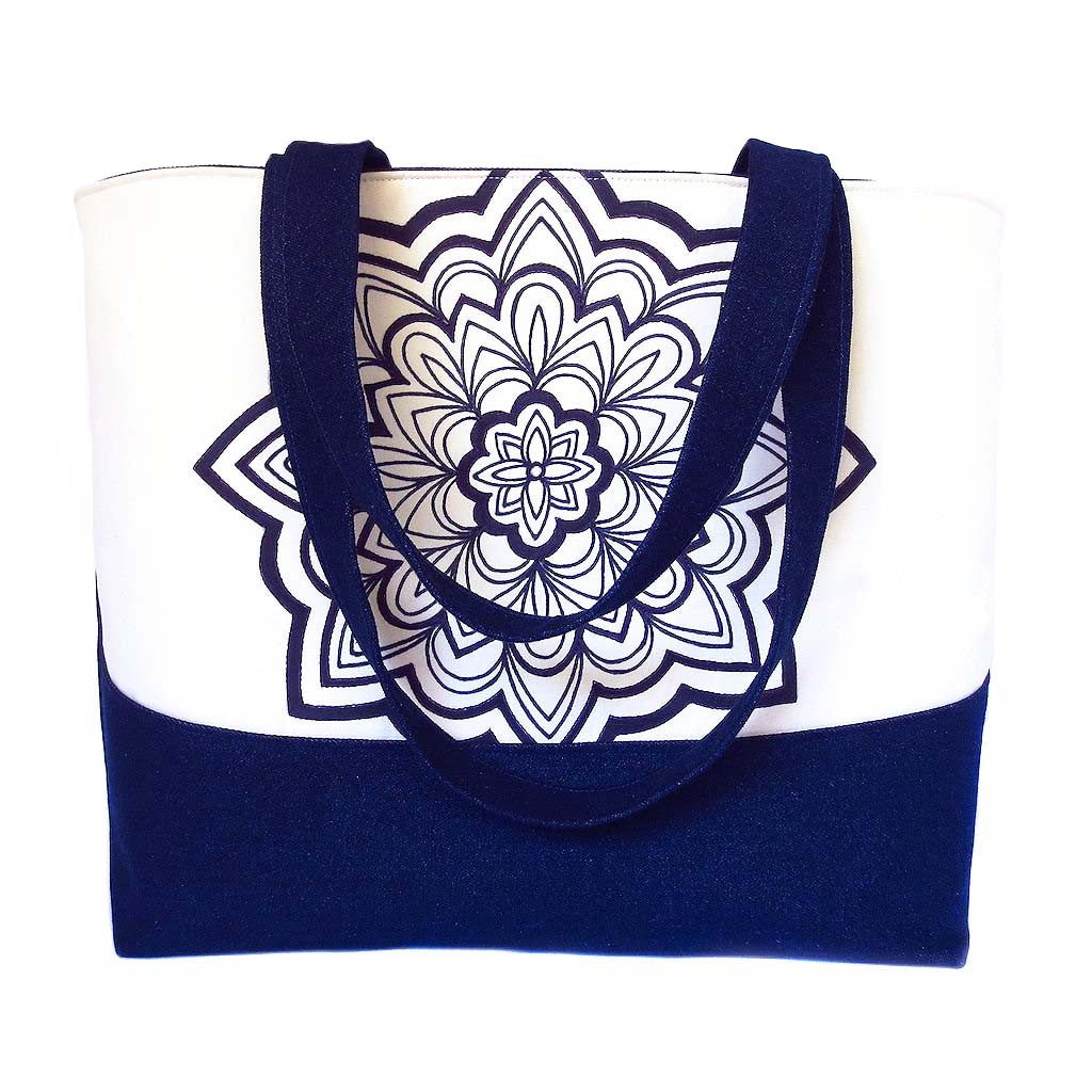 denim tote bag with hand drawn mandala motif in black ink, accented with purple stitching