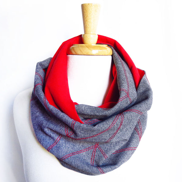 the cassandra infinity scarf is gray with a red chevron wave motif stitched in red, and is lined with red flannel