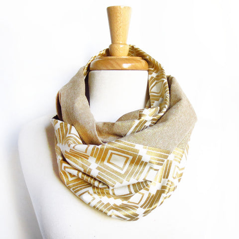 the naomi scarf is an infinity scarf made from gold metallic essex linen and a very bold white and gold graphic print, joined together with a diagonal seam