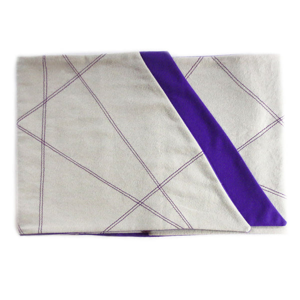 gray flannel scarf for men is folded to show off purple lining, stitched design, and angled edges