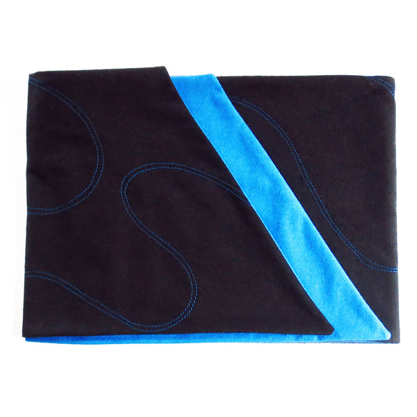 black flannel scarf folded to show off blue lining, angled edges, and blue stitching