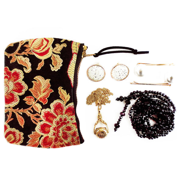 the phoenix mini pouch shown with a small set of jewelry that could easily fit inside - two necklaces, a set of earrings, and a pair of pearl hair pins