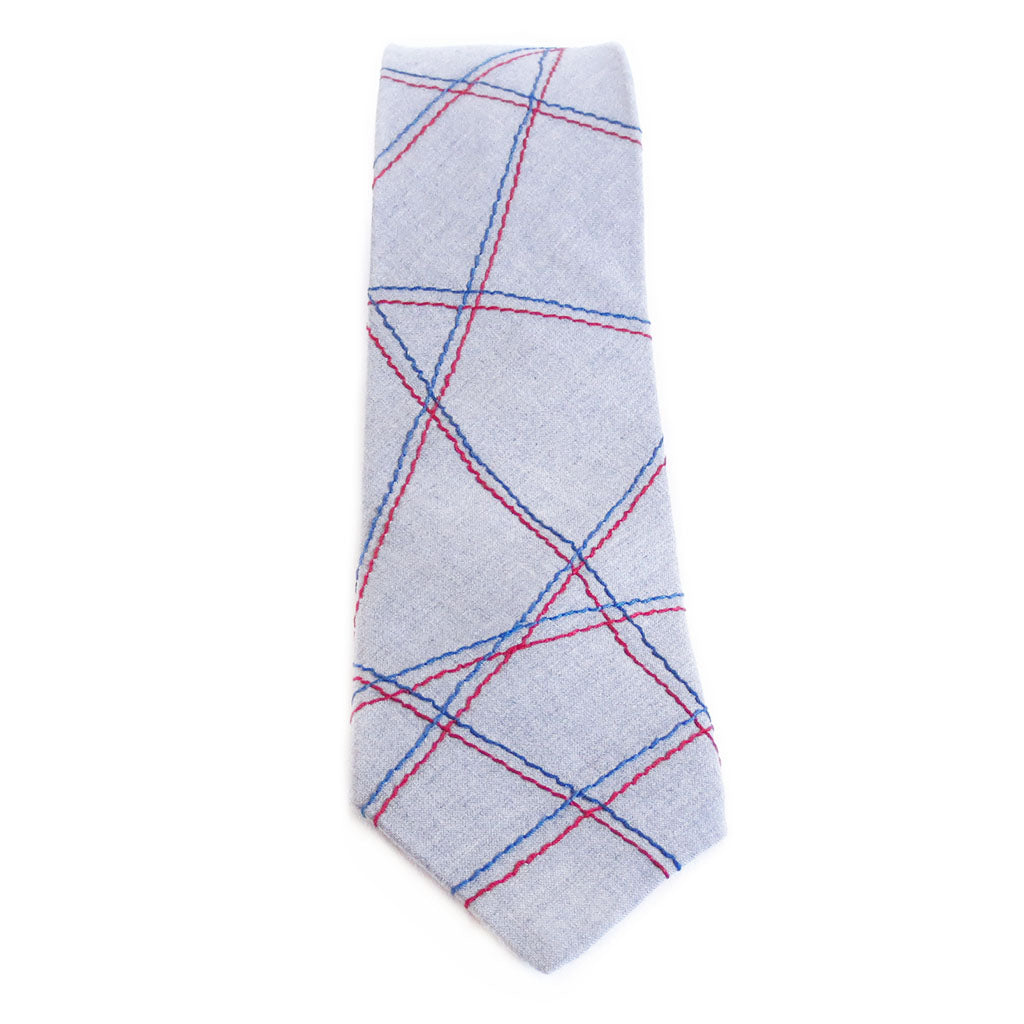 Handmade cotton blend necktie in light gray, stitched with abstract linear pattern in red and blue.