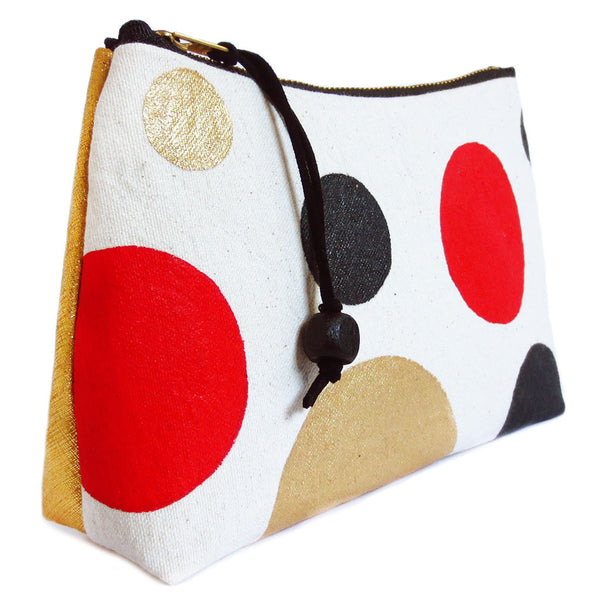 side view of gold leather and painted polka dot canvas zip pouch
