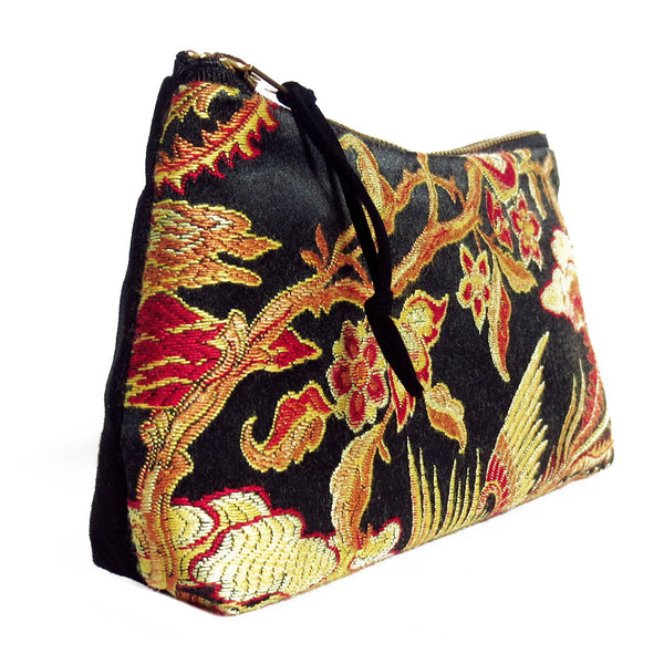 side view of zip pouch with gold and red damask paired with black denim