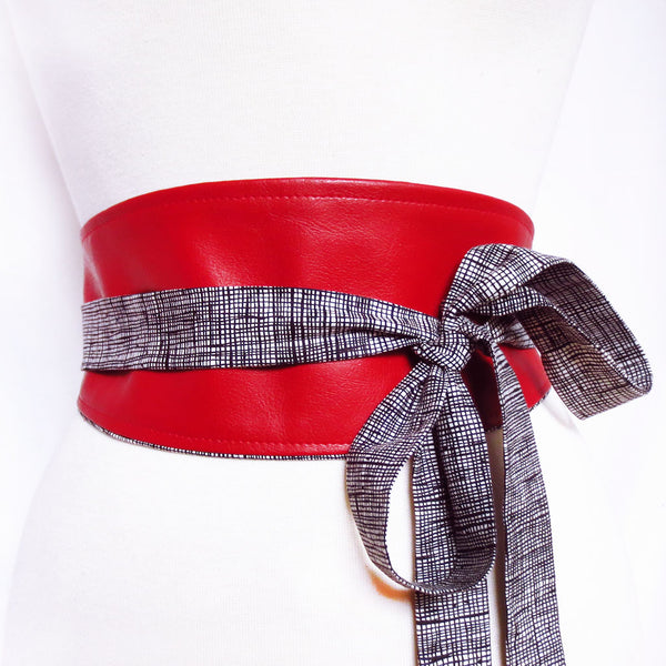 Obi style wrap belt in red vinyl with long ties in black and white crosshatch print, tied in a loose bow off to one side