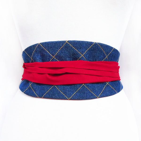 Denim obi style belt stitched with windowpane check in gold stitching, with long red ties wrapped and tied in the back.