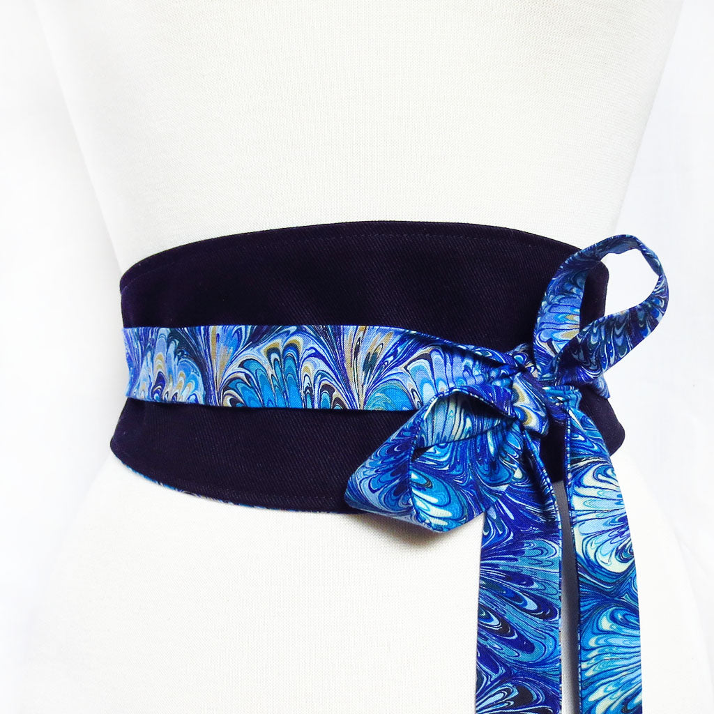 black denim obi style belt with long ties in a blue book marble print cotton, tied in a bow off to one side