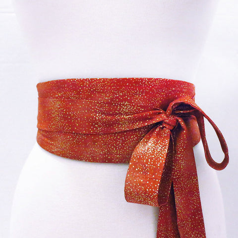 Josephine belt wrapped to show the printed side, tiny gold dots scattered on a warm red background. Long ties are tied in a large loose bow to one side.