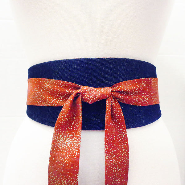 the Josephine wrap belt wrapped to show the denim side flecked with gold. Long ties in red and gold print are tied in a knot in the center front.