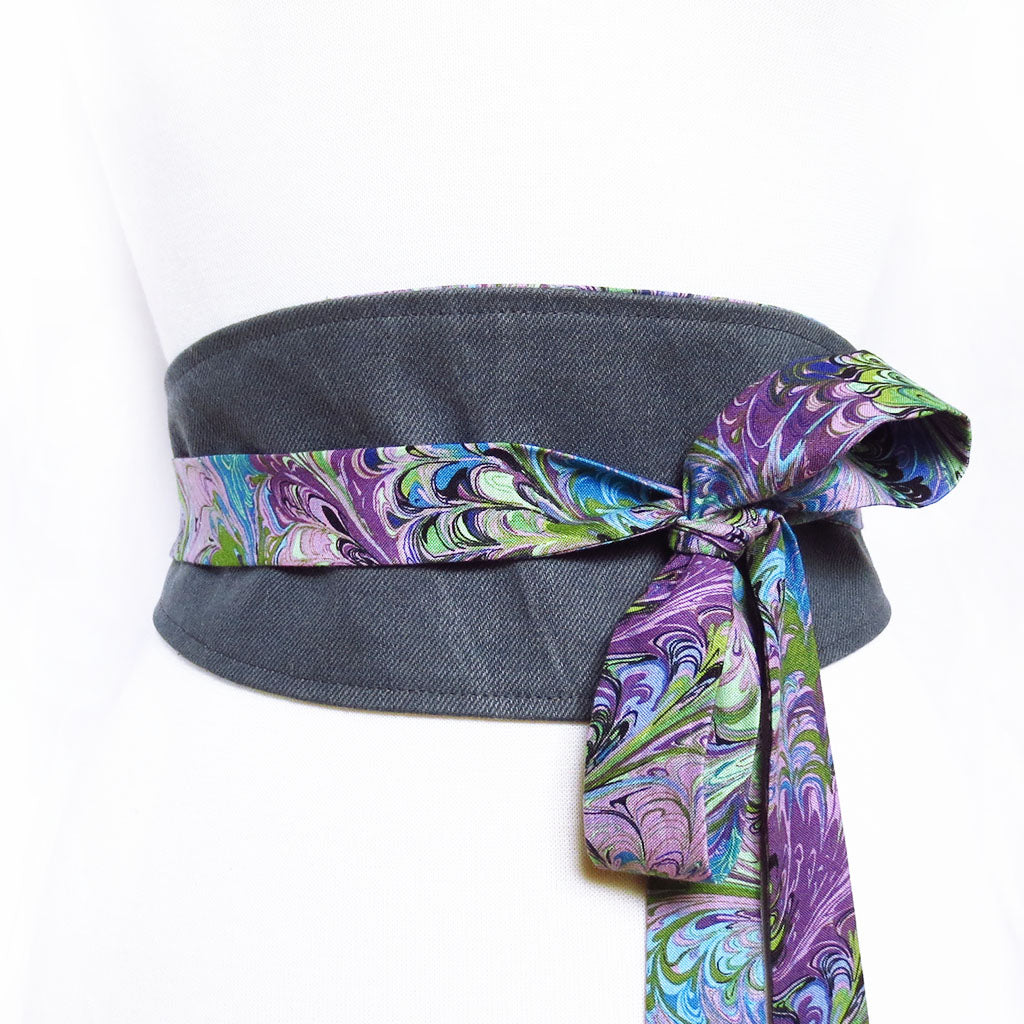 dark gray denim obi style belt with long ties in purple book marble print; tied off to one side in a loose bow