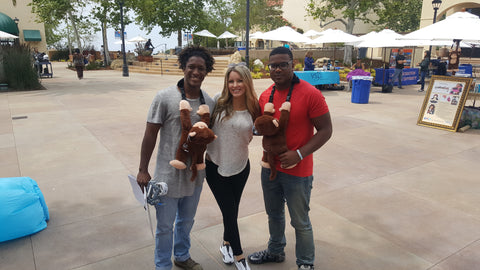 Warmkins Owner Founder Carolyn Rene' Garrick two male friends Pepperdine University Student smiles hugs Warmkins Hugo Monkey Therapeutic Weighted Sensory Heatable Microwavable Healing Hugs Stuffed Animal at the Health and Wellness Fair