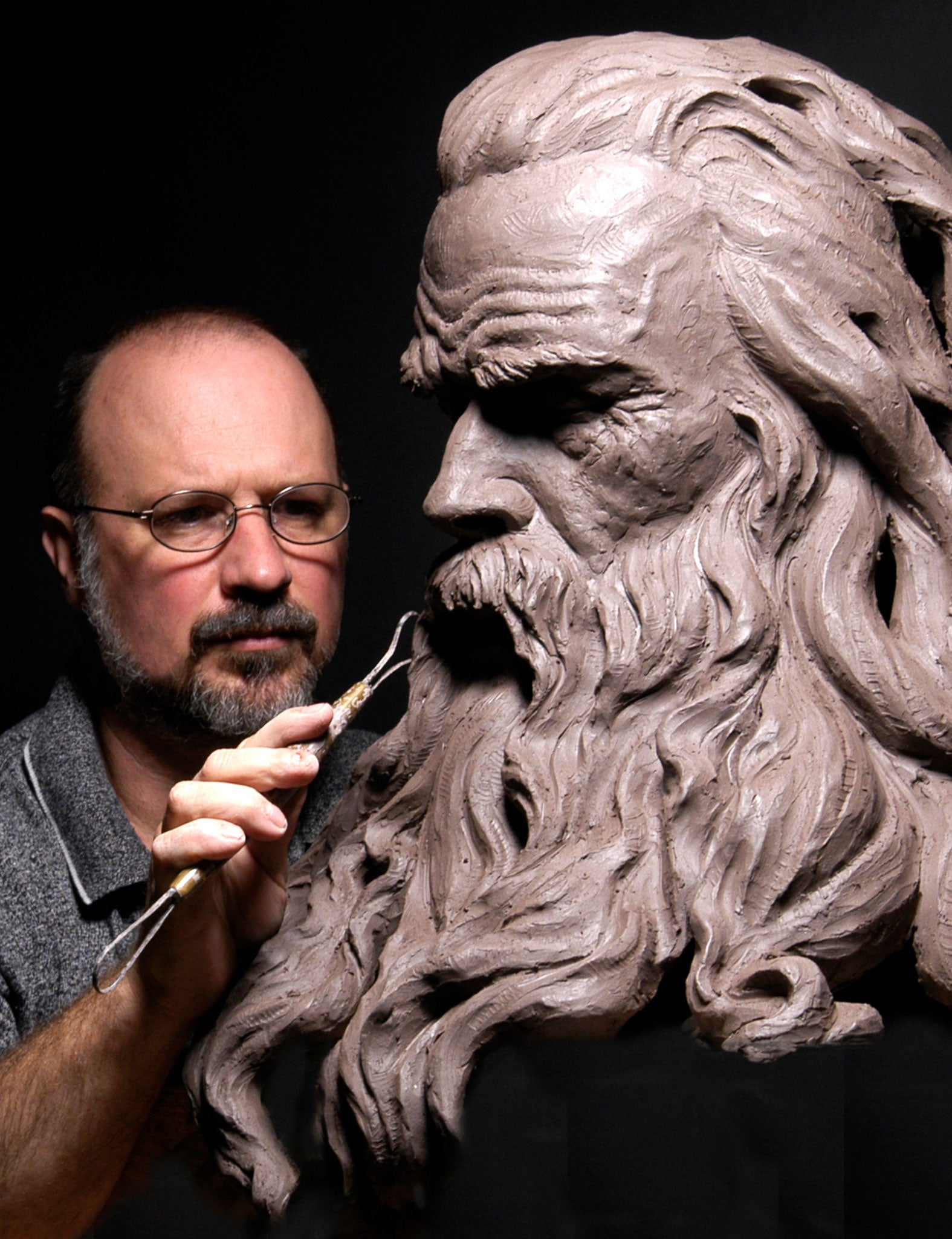 Philippe Faraut sculpting over-sized clay bust of man with beard for sculpting workshops