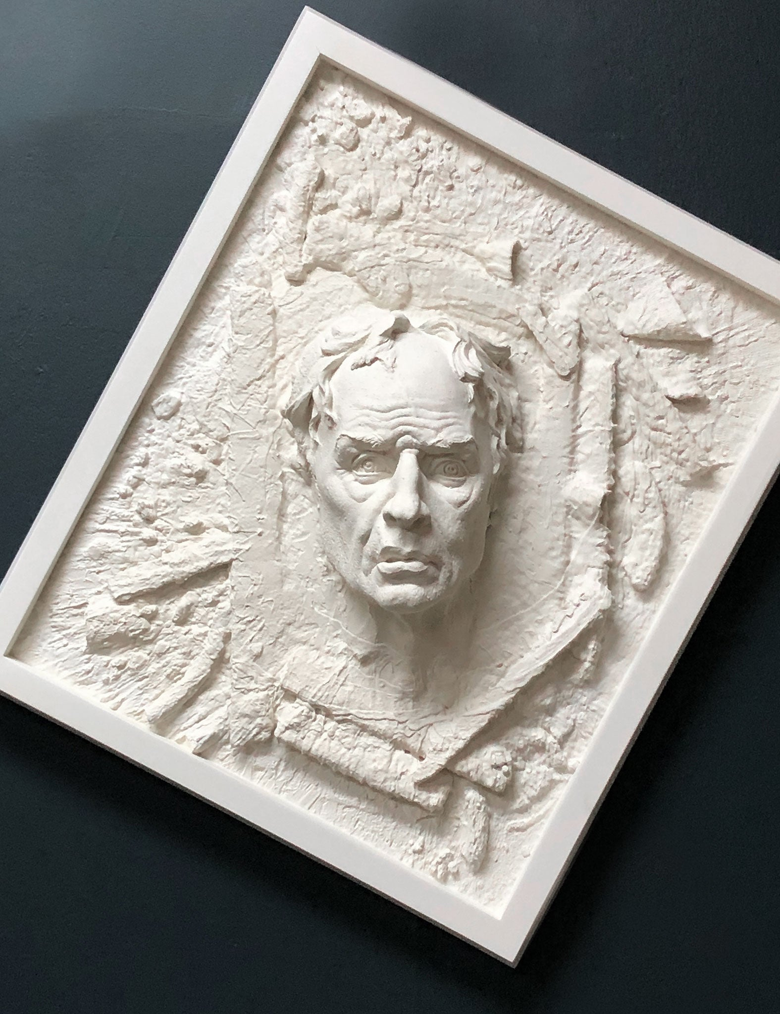 Plaster wall sculpture of abstract crazy man in frame by Philippe Faraut