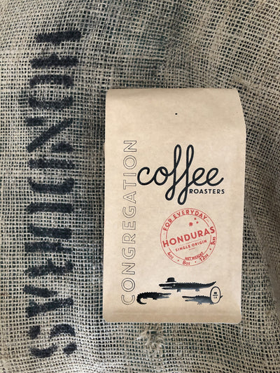 A 12oz bag of coffee is photographed on top of a burlap coffee sack. The coffee bag is brown kraft with a black hot stamp leaving a shiny black print of the company name and branded logo of 3 alligators. The Print says Congregation Coffee Roasters. There is also a round red stamp in the middle with the specific coffee inside the bag - the Honduras Single Origin - it says.