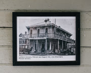 "Framed Black and white vintage newspaper photograph of the building that Congregation Coffee Roasters operates out of . There are 2 horse drawn carriages outside the corner store at the time. The text on the photograph says ""Lafitte's Grocery, Pelican and Seguin Sts., now Brechtel's Pelican Grocery."" Date of photograph unknown."
